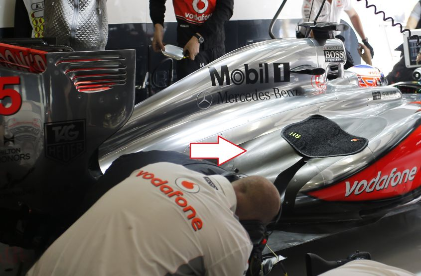 The team work on the car of Jenson Button in the garage.